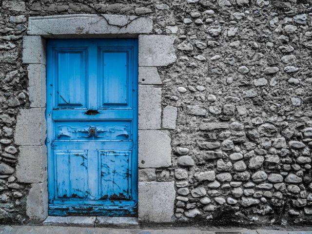 porte d'entrée bleu et mur en pierre